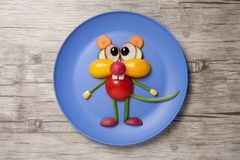Funny vegetable mouse made on plate and wooden background. Mouse made with fresh tomato, onion, cucumber, corn, radish and olive on blue plate and isolated Royalty Free Stock Photography