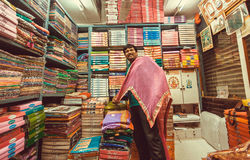 Funny vendor making presentation inside small textile store with dresses and scarfs stock images