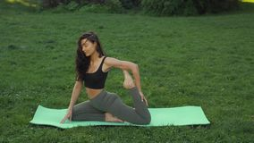 Funny video about young woman doing yoga exercise and fooling around outdoors in park at morning. stock video footage