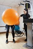 Funny exercise. Funny view of gymnastic ball exercise, made in electric muscle stimulation suit. Vertical shot Stock Photos