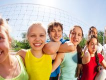Funny view of teens standing near volleyball net. Close funny view of cool teens standing near volleyball net holding ball on the game court  during summer sunny Royalty Free Stock Image