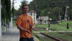 A young man claps his hands widely on a train station in Poland in slo-mo. A funny view of a young man with crew blond haircut who claps his hands widely on a stock video footage