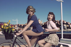 Funny vintage girls on bicycle near the sea Royalty Free Stock Images