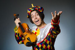 Funny violin clown player in musical concept Stock Photos