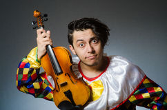 The funny violin clown player in musical concept Stock Photo