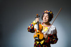 The funny violin clown player in musical concept Stock Photos
