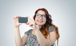 Funny viper girl with a smartphone on background Stock Photography
