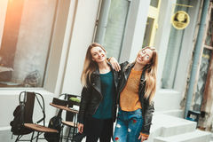 It is funny walk with best friend! Two beautiful women walking outdoor hugging and laughing on autumn street. Fashion urban girls spending weekend talking at stock photography
