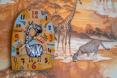 Funny wall clock with giraffe in kids room. Close up colorful wall clock with giraffe hanging on wall with safari wallpaper royalty free stock photo