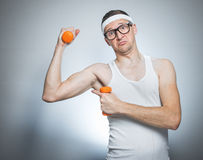Funny weak man lifting biceps Royalty Free Stock Image