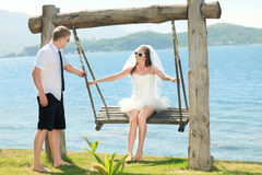 Funny wedding. Bride and groom on a swing Stock Photography