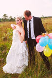 Funny wedding couple with balloons Stock Photos