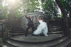 Funny wedding couple. Dancing on a stairs stock photography