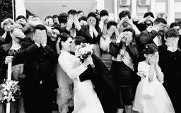 Funny wedding formal picture. Almost all group wedding photos are the same where all the people are staring at the camera. This is a black and white funny stock photo