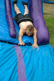 Funny Wet Slide. Grown adult man taking the plunge and going down a water slide royalty free stock photography
