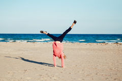 Funny white Caucasian child kid teenager, doing cartwheel playing on beach on sunset stock photos