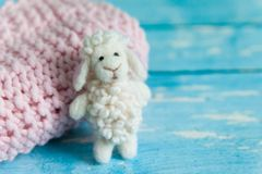 Funny white needle felted sheep. Funny white felted sheep on pink knit blanket on blue wooden background. Easter lamb stuffy stock photography
