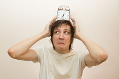 Funny white man hold on head alarm clock Royalty Free Stock Images