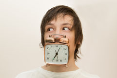 Funny white man hold in mouth  alarm clock Royalty Free Stock Images