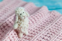 Funny white needle felted sheep. Funny white felted sheep on pink knit blanket on blue wooden background. Easter lamb stuffy stock image