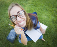 Funny Wide Angle of Nerdy Teen with Books and Pencil Royalty Free Stock Photos