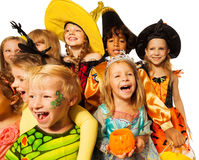 Funny wide angle shoot of kids in costumes. Funny wide angle portraits of large group of kids in Halloween costumes laughing and smiling, close-up studio shoot Royalty Free Stock Image