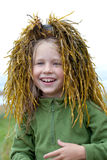Funny wig. Portrait of funny little girl with a wig from green seaweed on her head Royalty Free Stock Photos