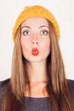 Funny winter face. Blonde girl in grey dress and yellow wool cap making funny face with lips like fish mouth. Surprised and shocked Royalty Free Stock Photography