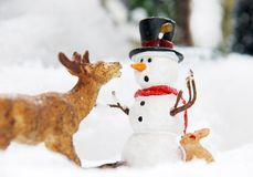 Funny winter snowman. Humorous still life of a poly stone snowman and a deer eating the snowmans carrot nose stock image