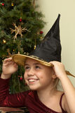 Funny witch. Portrait of smiling little girl in witch hat at christmas tree Royalty Free Stock Photography
