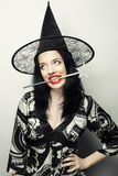 Funny Witch. Young happy woman with canival hat. Studio shot stock image