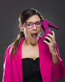 Funny woman. Middle aged woman holding a shoe pretending it's a cell phone stock photography