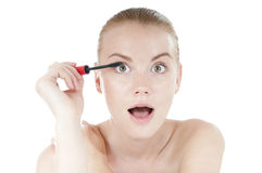 Funny woman applying cosmetics mascara brush. Stock Photos