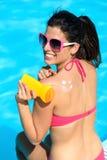 Funny woman applying sunscreen on summer stock photos