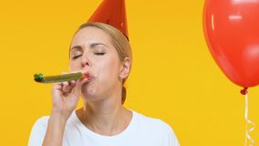Funny woman in birthday hat holding balloon and whistling in blow tickler, party. Stock footage stock video