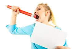 Funny woman biting big pencil. Funny nervous woman being stressed out about work or school. Teenage female holding piece of paper and biting big oversized pencil royalty free stock images