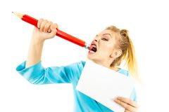 Funny woman biting big pencil. Funny nervous woman being stressed out about work or school. Teenage female holding piece of paper and biting big oversized pencil stock image