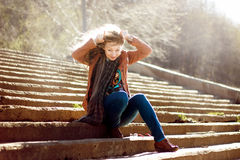 Funny woman with blonde curly hair on stairs background Stock Photo
