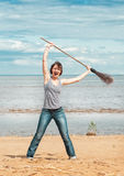 Funny woman with broom on the beach Stock Images