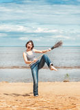 Funny woman with broom on the beach Royalty Free Stock Photography