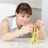 Funny woman building a tower with domino Stock Photography