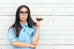 Funny Woman Checking Her Hair For Split Ends. Cute brunette girl with long hair in need for a urgent hair cut Royalty Free Stock Photo