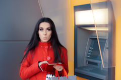 Funny Woman Checking her Wallet in Front of a Bank ATM Stock Photo