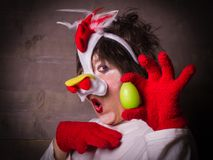 Funny woman in chicken costume. Expression woman in chicken costume with egg. Which came first - Chicken or Egg Stock Photo