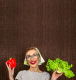 Funny woman cook. Holding salad and sweet pepper, space for yuor text Stock Photography