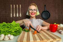 Funny woman cook. Happy funny woman cook working in the kitchen cutting carrot Stock Photography