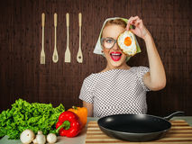Funny woman cook. Happy funny woman cook holding pan with fried egg - close up Royalty Free Stock Images