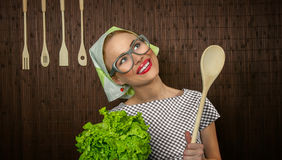 Funny woman cook. Funny rural woman cook holdin ledle and salad, close-up Stock Photo