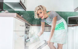 Funny woman cook frying or roasting something in a oven. Smoke, vapor around in the kitchen or home royalty free stock image