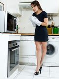 Funny woman cooking. Beautiful caucasian woman in a kitchen waiting with anxiety in front of the oven Stock Images